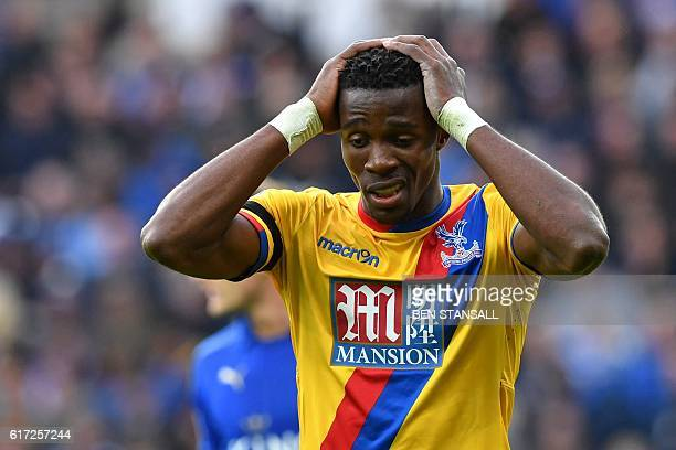 Crystal Palace's Ivorianborn English striker Wilfried Zaha reacts after missing a chance during the English Premier League football match between...