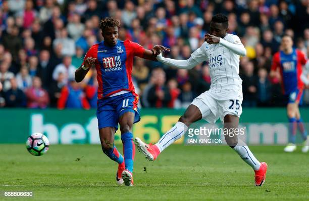 Crystal Palace's Ivorianborn English striker Wilfried Zaha vies with Leicester City's Nigerian midfielder Wilfred Ndidi during the English Premier...