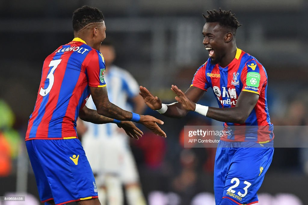 Crystal Palace's Senegalese defender Pape Souare (R) gestures to Crystal Palace's Dutch defender Patrick van Aanholt as he starts the second half after missing most of last season, during the English League Cup third round football match between Crystal Palace and Huddersfield Town at Selhurst Park in south London on September 19, 2017. / AFP PHOTO / Glyn KIRK / RESTRICTED TO EDITORIAL USE. No use with unauthorized audio, video, data, fixture lists, club/league logos or 'live' services. Online in-match use limited to 75 images, no video emulation. No use in betting, games or single club/league/player publications. /