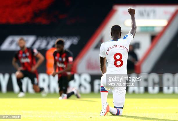 Crystal Palace's Senegalese midfielder Cheikhou Kouyate takes a knee to show support for the Black Lives Matters movement and as a protest against...