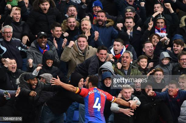 Crystal Palace's Serbian midfielder Luka Milivojevic celebrates with the crowd after scoring his and his team's second goal to equalise 22 during the...