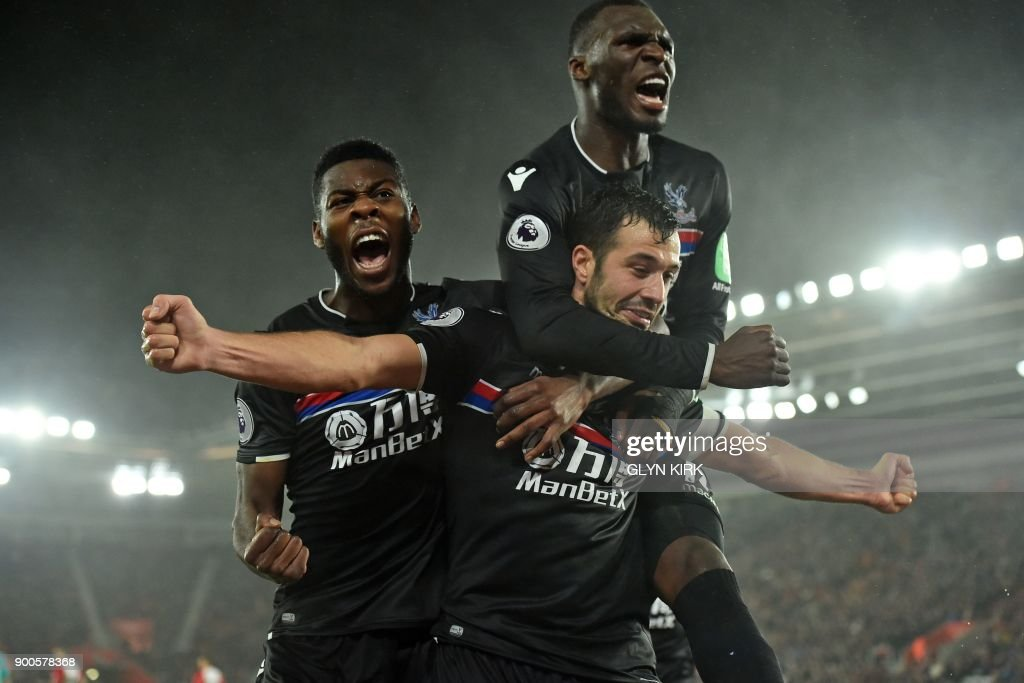 TOPSHOT - Crystal Palace's Serbian midfielder Luka Milivojevic celebrates with Crystal Palace's Dutch defender Timothy Fosu-Mensah (L) and Crystal Palace's Zaire-born Belgian striker Christian Benteke after scoring their second goal during the English Premier League football match between Southampton and Crystal Palace at St Mary's Stadium in Southampton, southern England on January 2, 2018. / AFP PHOTO / Glyn KIRK / RESTRICTED TO EDITORIAL USE. No use with unauthorized audio, video, data, fixture lists, club/league logos or 'live' services. Online in-match use limited to 75 images, no video emulation. No use in betting, games or single club/league/player publications. /