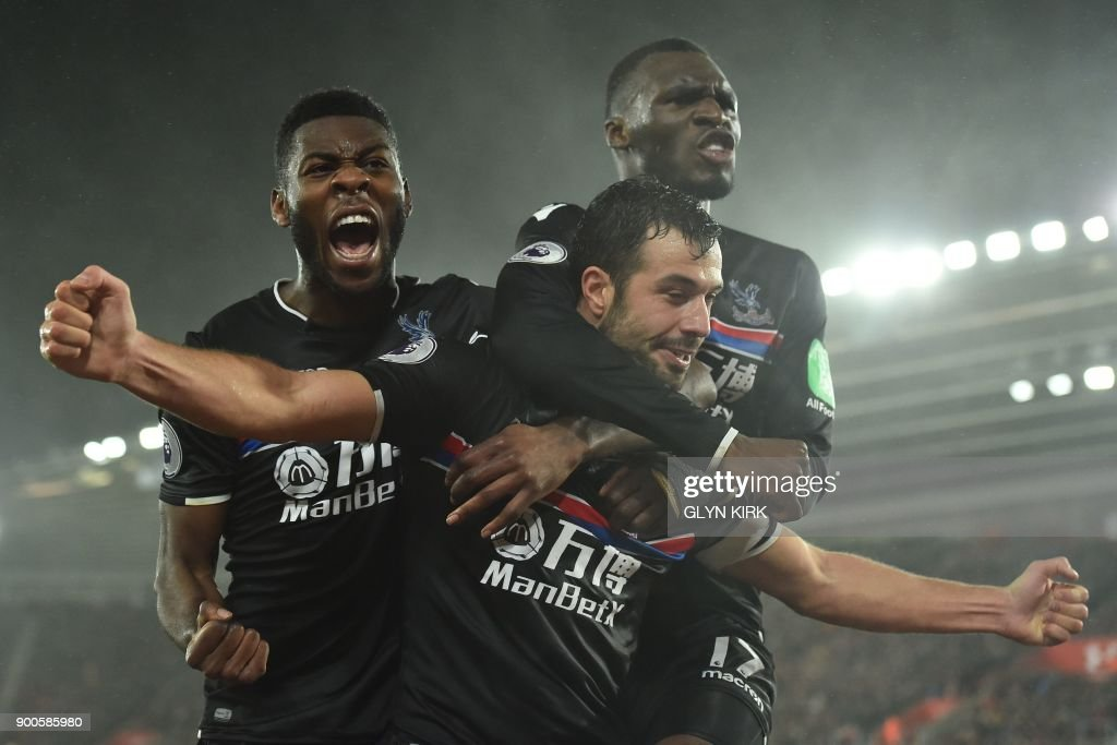 Crystal Palace's Serbian midfielder Luka Milivojevic celebrates with Crystal Palace's Dutch defender Timothy Fosu-Mensah (L) and Crystal Palace's Zaire-born Belgian striker Christian Benteke (R) after scoring their second goal during the English Premier League football match between Southampton and Crystal Palace at St Mary's Stadium in Southampton, southern England on January 2, 2018. / AFP PHOTO / Glyn KIRK / RESTRICTED TO EDITORIAL USE. No use with unauthorized audio, video, data, fixture lists, club/league logos or 'live' services. Online in-match use limited to 75 images, no video emulation. No use in betting, games or single club/league/player publications. /