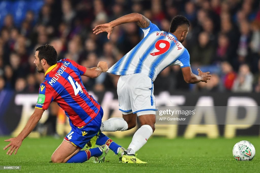 Crystal Palace's Serbian midfielder Luka Milivojevic (L) is booked for this challenge on Huddersfield Town's German striker Elias Kachunga during the English League Cup third round football match between Crystal Palace and Huddersfield Town at Selhurst Park in south London on September 19, 2017. / AFP PHOTO / Glyn KIRK / RESTRICTED TO EDITORIAL USE. No use with unauthorized audio, video, data, fixture lists, club/league logos or 'live' services. Online in-match use limited to 75 images, no video emulation. No use in betting, games or single club/league/player publications. /