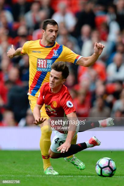 Crystal Palace's Serbian midfielder Luka Milivojevic tackles Manchester United's English midfielder Josh Harrop during the English Premier League...