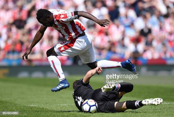 Crystal Palace's Serbian midfielder Luka Milivojevic vies with Stoke City's Senegalese striker Mame Biram Diouf during the English Premier League...