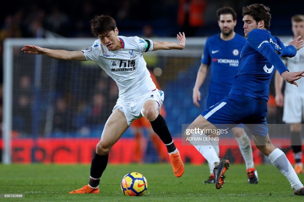 TOPSHOT - Crystal Palace's South Korean midfielder Lee Chung-yong (L) takes on Chelsea's Spanish defender Marcos Alonso (R) during the English Premier League football match between Chelsea and Crystal Palace at Stamford Bridge in London on March 10, 2018. / AFP PHOTO / Adrian DENNIS / RESTRICTED TO EDITORIAL USE. No use with unauthorized audio, video, data, fixture lists, club/league logos or 'live' services. Online in-match use limited to 75 images, no video emulation. No use in betting, games or single club/league/player publications. /
