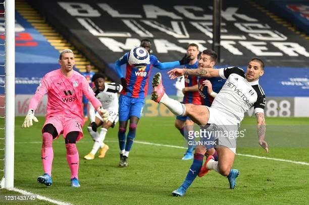 Crystal Palace's Spanish goalkeeper Vicente Guaita watches as Crystal Palace's English defender Joel Ward vies with Fulham's Serbian striker...