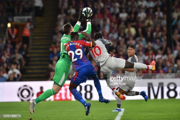 Crystal Palace's Welsh goalkeeper Wayne Hennessey claims the ball as Crystal Palace's English midfielder Aaron WanBissaka and Liverpool's Senegalese...