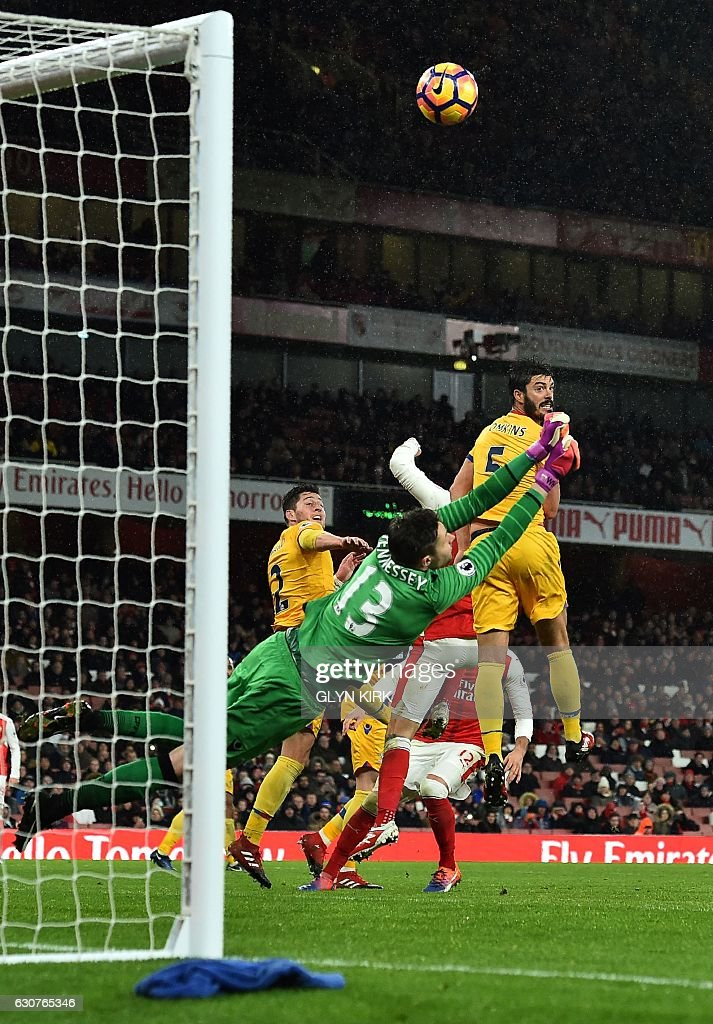 Crystal Palace's Welsh goalkeeper Wayne Hennessey dives to save a freekick during the English Premier League football match between Arsenal and Crystal Palace at the Emirates Stadium in London on January 1, 2017. Arsenal won the match 2-0. / AFP / Glyn KIRK / RESTRICTED TO EDITORIAL USE. No use with unauthorized audio, video, data, fixture lists, club/league logos or 'live' services. Online in-match use limited to 75 images, no video emulation. No use in betting, games or single club/league/player publications. /