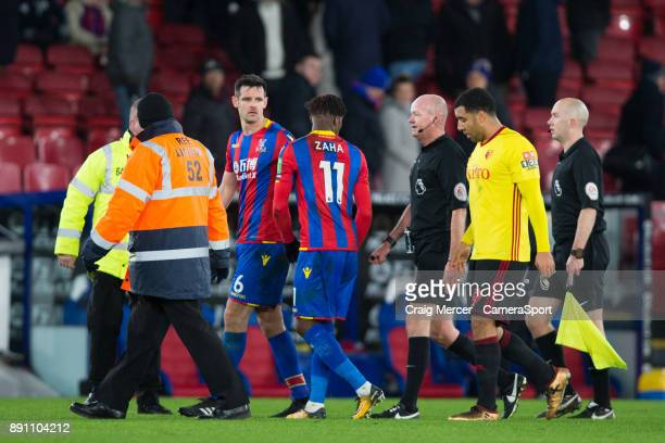 Crystal Palace's Wilfried Zaha continues to have discussions with Referee Lee Mason as the players walk off for half time during the Premier League...