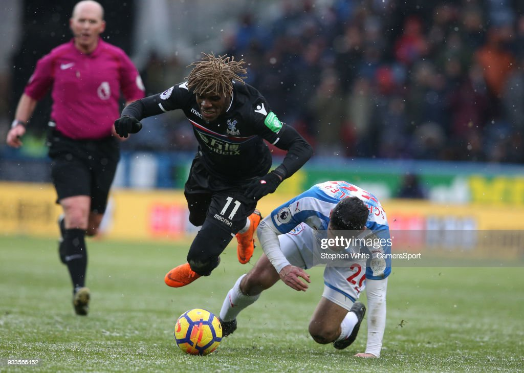 Crystal Palace's Wilfried Zaha is tackled by Huddersfield Town's Christopher Schindler during the Premier League match between Huddersfield Town and Crystal Palace at John Smith's Stadium on March 17, 2018 in Huddersfield, England.
