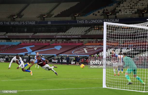 Crystal Palace's Zaire-born Belgian striker Christian Benteke heads the ball and scores a goal during the English Premier League football match...
