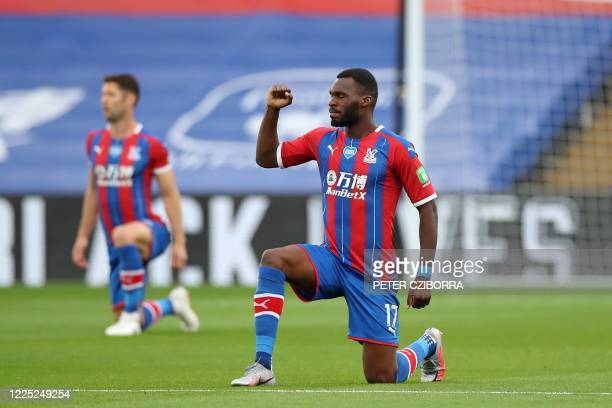 Crystal Palace's Zaireborn Belgian striker Christian Benteke takes a knee to show solidarity with the Black Lives Matter movement and to protest...
