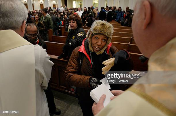 Crystal Priest receives twenty dollars during the Father Woody money giveaway at the Cathedral Basilica of the Immaculate Conception in Denver, CO...