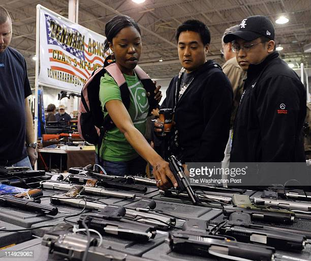 Crystal Smith of Ashburn handles a pistol at the Nation's Gun Show in April With her are her friends Bobby Nguyen center of Herndon and Rob Barba of...