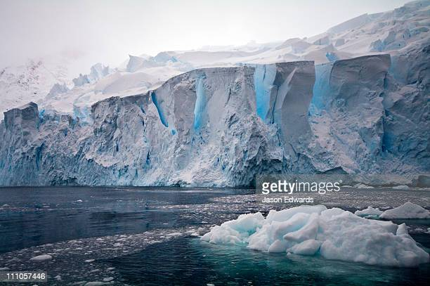 the fracture zone of massive glacial ice cliffs teeter over icy seas. - drift ice stock pictures, royalty-free photos & images