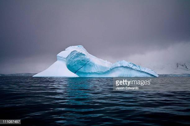 An iridescent iceberg floating in a dark sea beneath stormy skies.