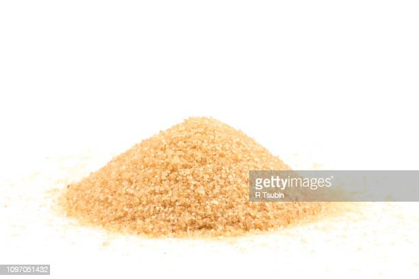 crystals cane brown sugar isolated on white background - icing sugar stock pictures, royalty-free photos & images