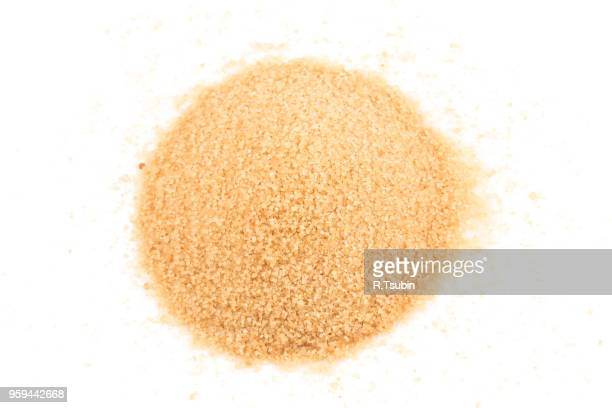 crystals cane brown sugar isolated on white background - sugar pile stock pictures, royalty-free photos & images