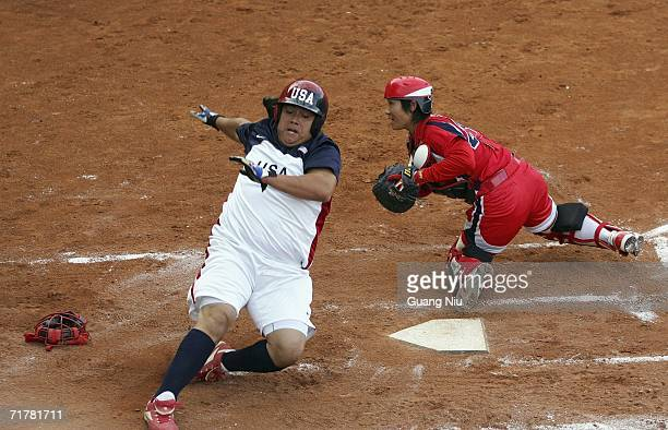 Crystl Bustos of USA runs to the home plate as Emi Inut of Japan catches a ball at ISF XI Women's Fast Pitch Softball World Championship at the...