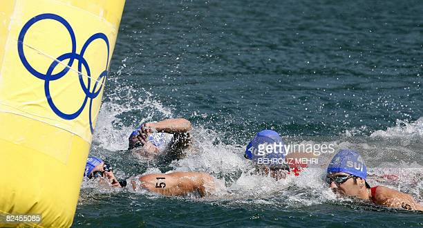 Csaba Kuttor of Hungary Simon Agoston of Austria and Sven Riederer of Switzerland swim along the Ming tomb reservoir during the men's triathlon...