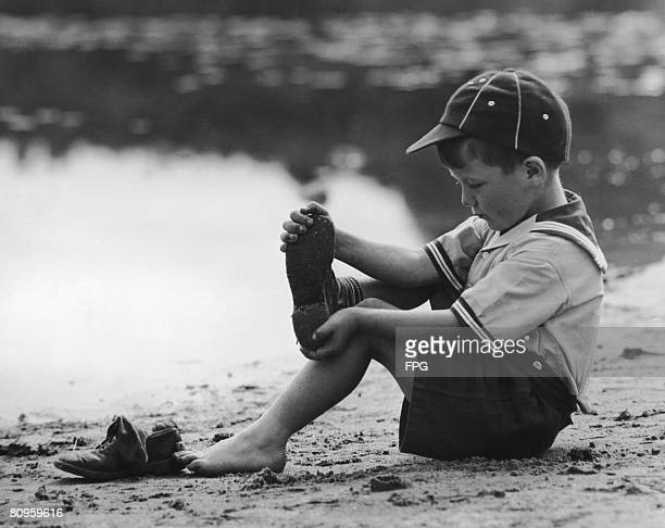 A cub scout takes off his shoes and socks before going for a paddle circa 1955