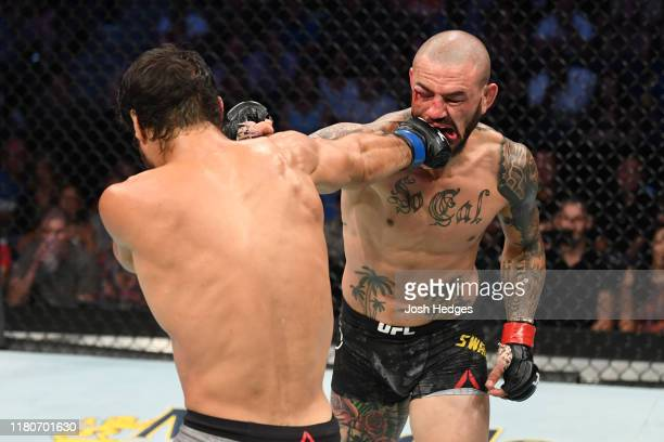 Cub Swanson and Kron Gracie of Brazil exchange punches in their featherweight bout during the UFC Fight Night event at Amalie Arena on October 12...