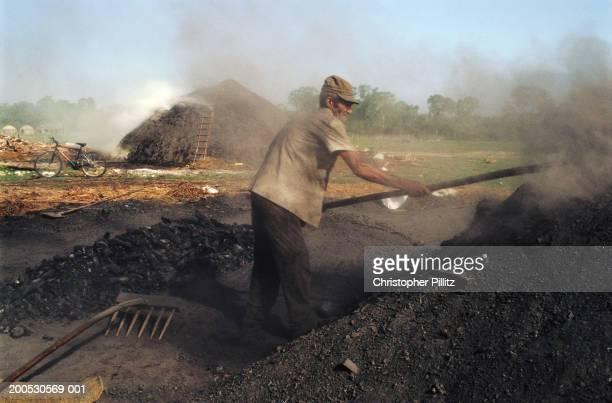 Cuba, Cayo Ramon, man raking coal heap in field.