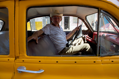 Cuba, Havana, senior man in driving seat of taxi, portrait - gettyimageskorea