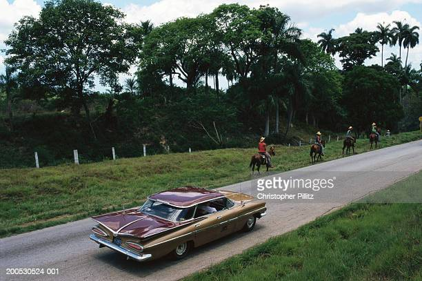 Cuba, horsemen and car on road towards Trinidad Town, elevated view