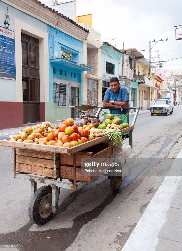 Cuba incipient market society: Street fruit seller carries ...