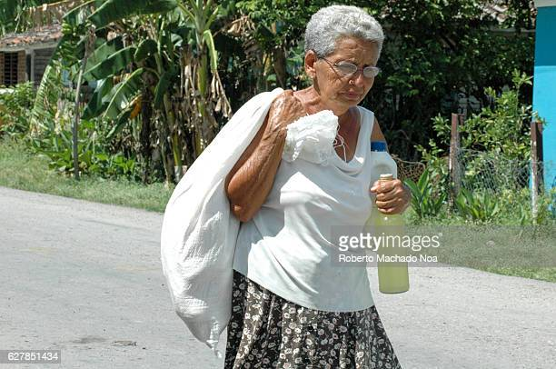 Cuba lifestyle or way of living Old lady carrying a bag over her shoulder and a bottle of lime juice