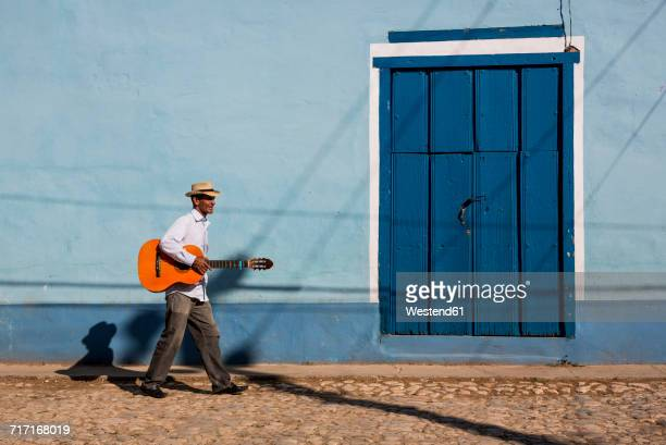 cuba, man with guitar walking on the street - cuba foto e immagini stock