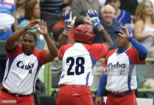 Cuba National baseball team infielder William Saavedra receives high fives from teammates Alfredo Despaigne and Yadiel Hernandez after scoring in the...