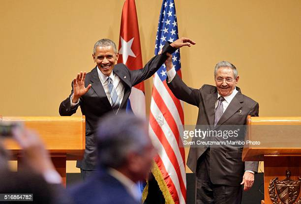Cuba President Raul Castro lifts the arm of US President Barack Obama at the end of a joint press conference at the Cuban State Council on March 21...