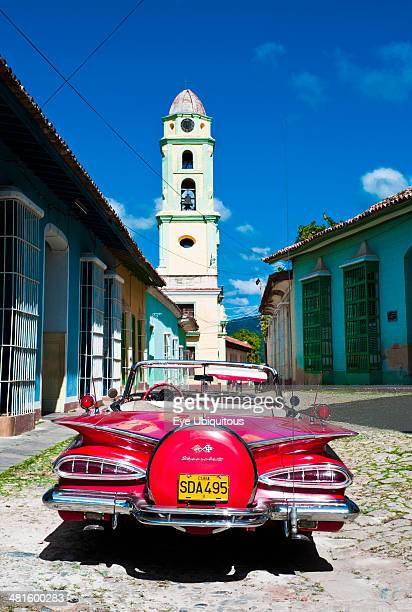 Cuba Sancti Spiritus Trinidad Red 1957 Chevrolet convertible car parked in cobbled street