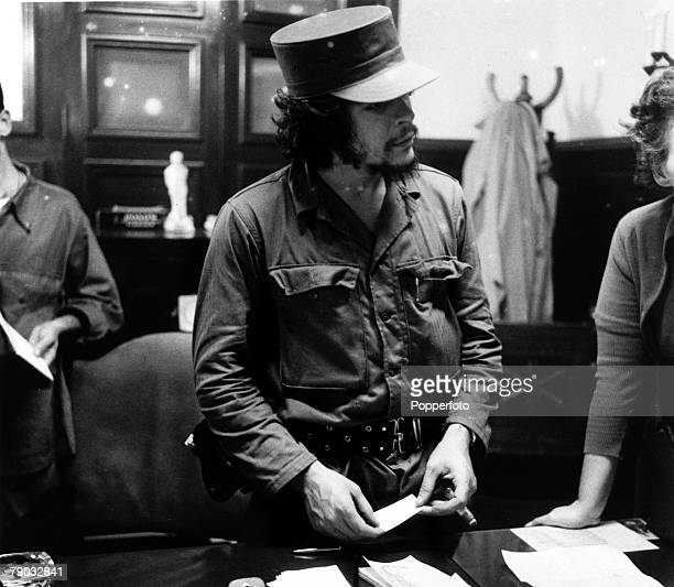 Cuba South America Circa 1960's A portrait of Argentine born Che Guevara the Cuban revolutionary political leader standing behind a desk in a busy...