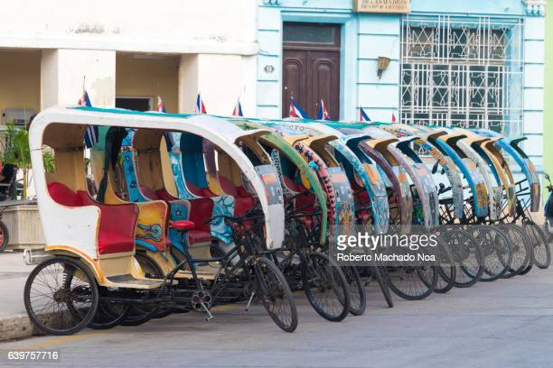 Cuba Tourism: Line of 'bicitaxis' or rickshaws waiting for tourist passengers at the Worker's plaza in Camaguey.