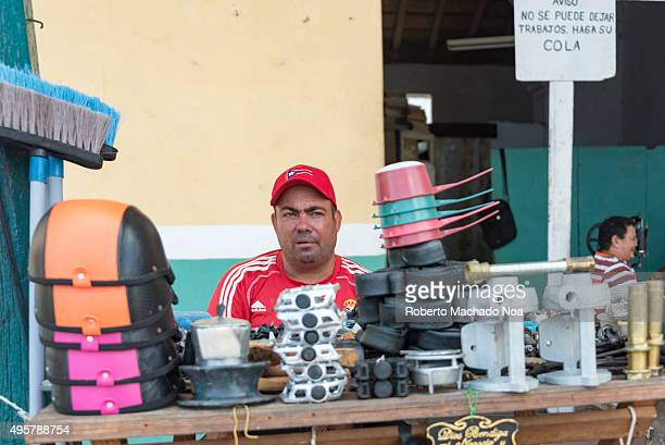 Cuba tourism Man selling hardware items made of plastic and metal on the street side in Sancti Spiritus Cuba