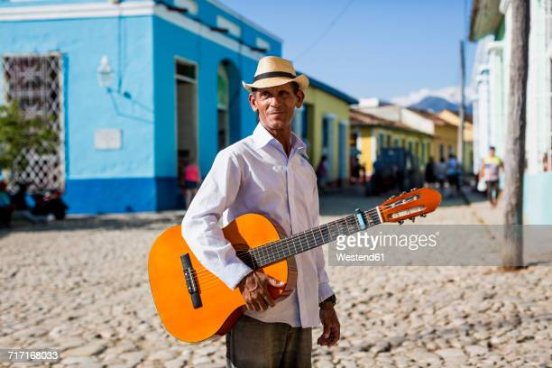 Cuba, Trinidad, man with guitar standing on the street