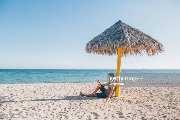 Cuba, Young man sitting under a sunshade at Playa Ancon