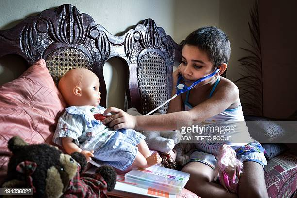 Cuban 6year old cancer patient Noemi Bernardez plays doctors in her house after being authorized at the Cancer Hospital to visit her family in Havana...