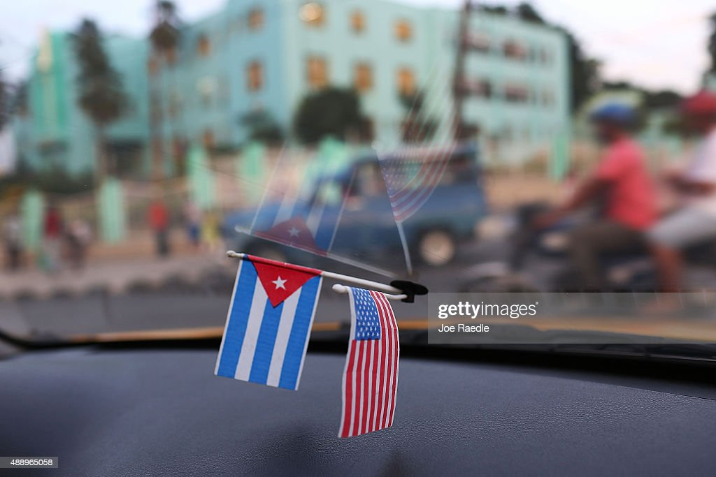 A Cuban and American flag are seen in the window of a taxi as Cuba prepares to welcome Pope Francis for a visit on September 18, 2015 in Santiago de Cuba, Cuba. Pope Francis is due to make a three day visit to Cuba from September 19 where he will meet President Raul Castro and hold Mass in Revolution Square before travelling to Holguin, Santiago de Cuba, El Cobre and onwards to the United States.