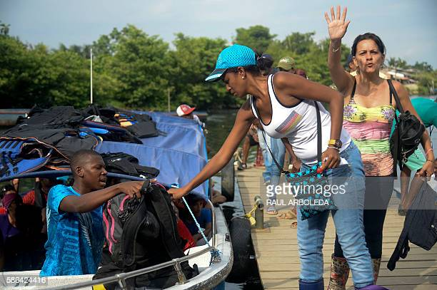 Cuban and Haitian migrants board a vessel to Capurgana in the Caribbean Gulf of Uraba in northwestern Colombia to illegally cross to Panama through...