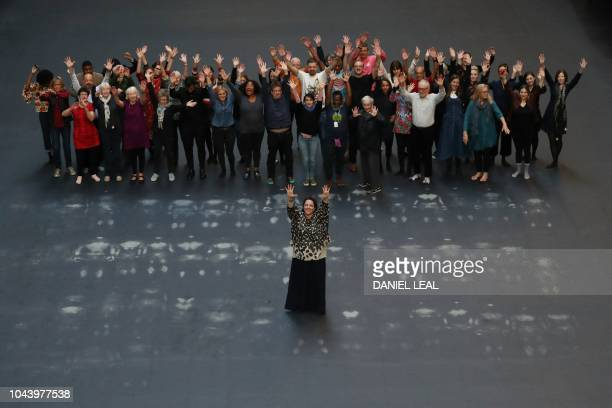 Cuban artist Tania Bruguera stands surrounded by volunteers in the Turbine Hall of the Tate Modern at the opening of her commission 'Tania Bruguera...