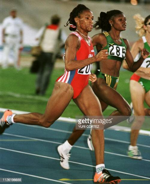 Cuban athlete Ana Fidelia Quirot runs in front of Charmaine Howell in the 800 meter semifinals17 August in the Pachencho Romero Stadium in Maracaibo...