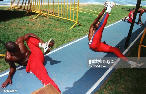 Cuban athletes Georkis Vera Jorge Crucellas and Omar Mena stretch during training for the 400 meter relay in the Panchencho Romero Stadium 14 August...