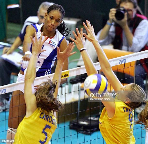 Cuban attacker Yumilka Ruiz spikes the ball past Brazilan defenders Caroline Gattaz Carolina Albuquerque at the World Grand Prix women's volleyball...