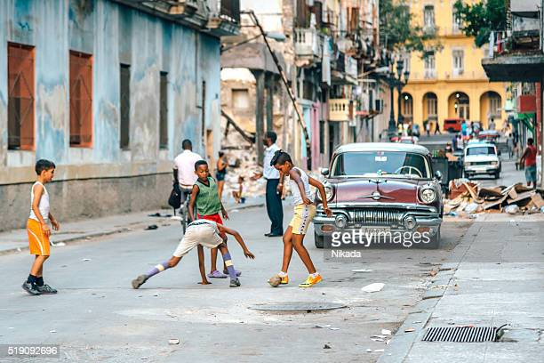 Cuban boys playing soccer on a dusty street in Havana.